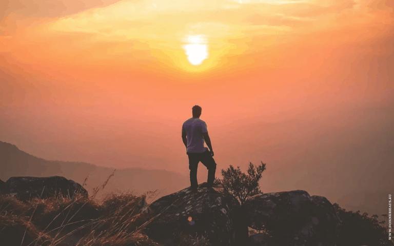 EIn Mann schaut vor einem orangenen Sonnenuntergang von einem Felsen in die Ferne.